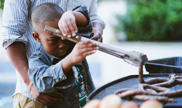 Young boy learning to use barbecue tongs with sausages