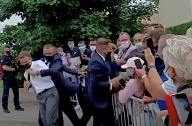 French President Emmanuel Macron is protected by a bodyguard after getting slapped by a member of the public during a visit in Tain-L'Hermitage, France, in this still image taken from video on June 8, 2021.