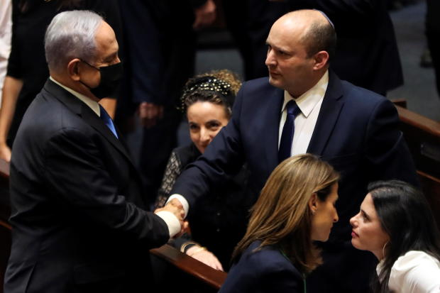 Head of Oposition Benjamin Netanyahu and Israel Prime minister Naftali Bennett shake hands following the vote on the new coalition at the Knesset, Israel's parliament, in Jerusalem