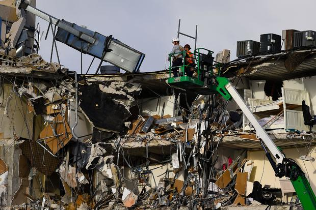 Rescue workers on a crane inspect the wreckage of the collapsed condo building in Surfside, Florida