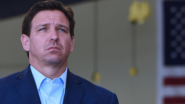Florida Governor, Ron DeSantis listens to another speaker at