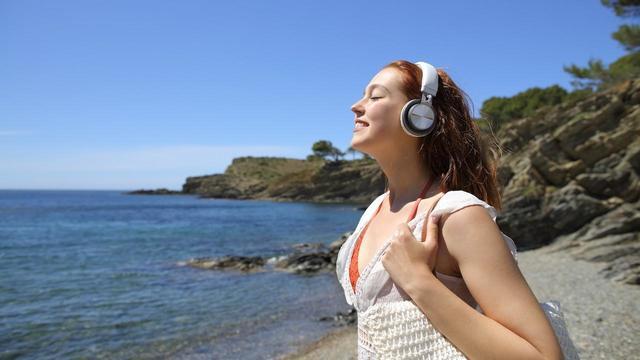 Person enjoying an audiobook on the beach