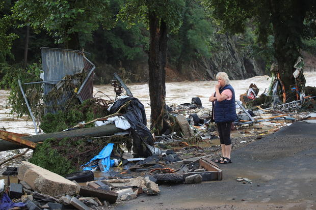 A woman looks at debris brought by the flood next to the Ahr river in Schuld