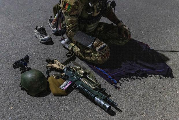Un miembro de las fuerzas especiales afganas reza en una carretera antes de una misión de combate contra los talibanes en la provincia de Kandahar.