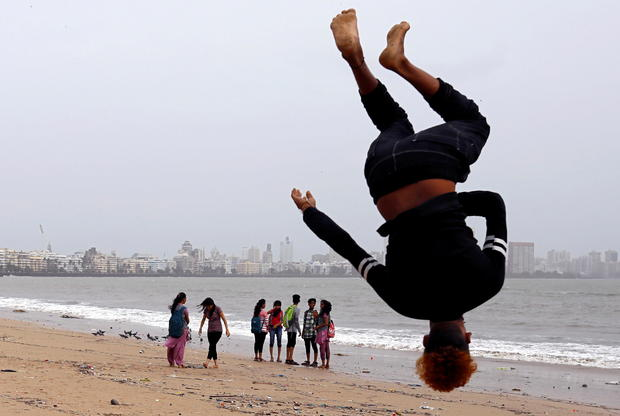 FILE PHOTO: Beachgoers stroll as a boy practices somersaulting on a beach in Mumbai