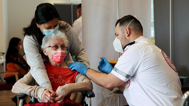 FILE PHOTO: An elderly woman receives a booster shot of her vaccination against the coronavirus disease (COVID-19) at an assisted living facility, in Netanya