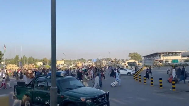 A horde of people run towards the Kabul Airport Terminal, after Taliban insurgents took control of the presidential palace in Kabul