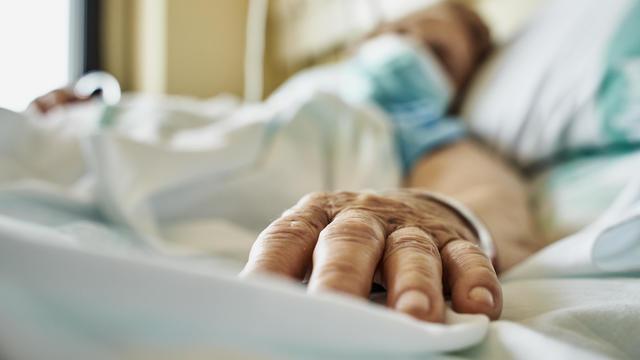 Senior woman wearing face mask lying on hospital bed