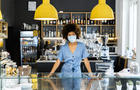 Young female owner wearing mask standing at counter in coffee shop