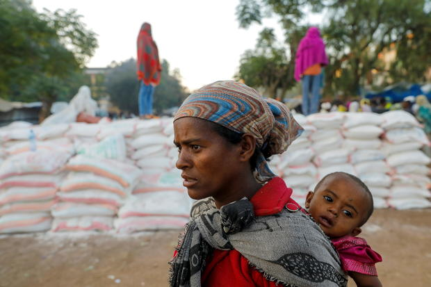 Woman carries an infant as she queues in line for food in Tigray region of Ethiopia