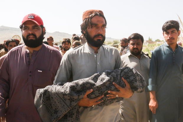 A man carries the body of a child, who died following an earthquake, during a funeral in Harnai