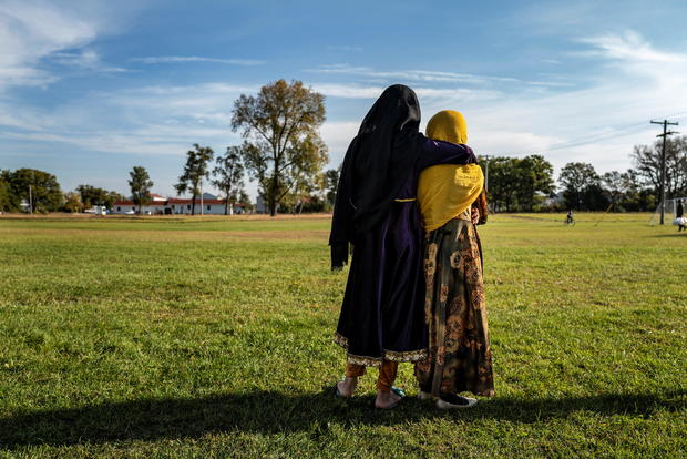 Afghan refugee girls watch a soccer match near where they are staying in the Village at the Fort McCoy, in Wisconsin