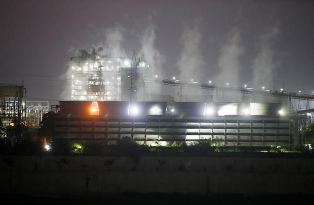 Smoke billows from the cooling towers of a coal-fired power plant in Ahmedabad