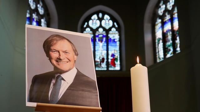 A candle and a portrait of British MP David Amess are seen at the church of St Michael's and all Angels, in Leigh-on-Sea