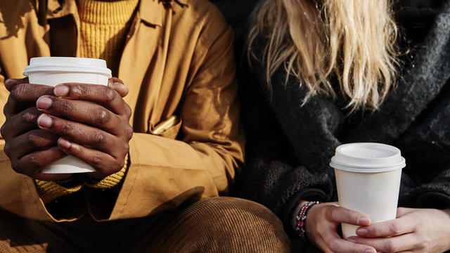 Friends holding a paper cup of coffee while sitting together. focus on the hands.