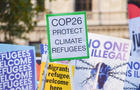 """A placard reading """"COP26 protect climate refugees"""""""
